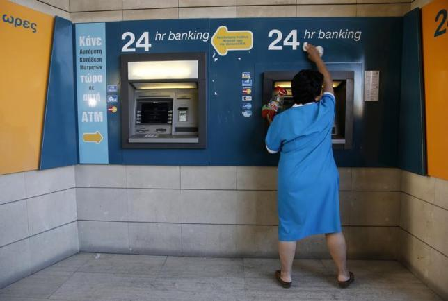 A cleaning lady wipes dust off an ATM in Nicosia